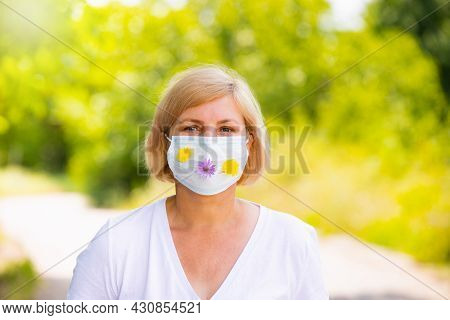 Close Up Photo Of A Pretty Blonde Woman Posing In A Medical Face Mask With Yellow And Violet Flowers
