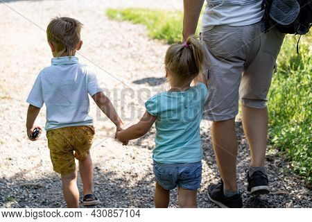 Backview Of Man Walking Alone Lane In Park With Children Holding Daughter By Hand