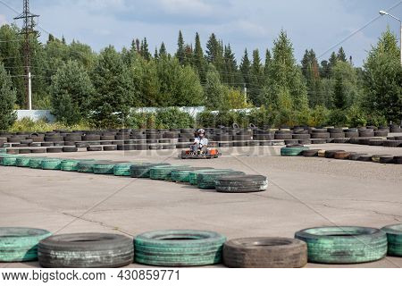 A Girl Or A Woman In A Helmet Rides A Go-kart On A Special Track.