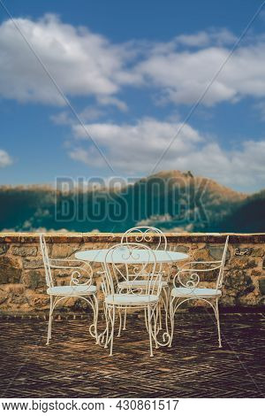 Small Table With White Chairs Overlooking The Terrace Of An Ancient Village. Valley With Mountains A