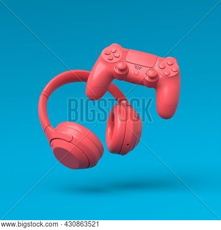 Flying Gamer Gears Like Headphones And Joystick On Blue And Pink Background