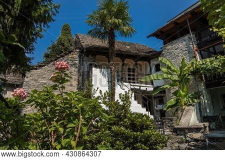 Exterior of a typical Ticinese house, in Switzerland, in the culeo of the village of Avegno. It is summer and there is a certain quietness of the surrounding environment.