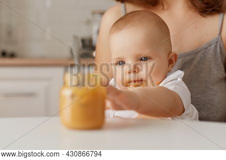 Portrait Of Cute Small Baby Sitting On Mother Knees Trying To Take Spoon With Vegetable Or Fruit Pur