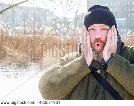 Man Breathing In Winter Forest. Adult Man Wearing Knit Hat, Put Hands On His Face And Breathing Cold