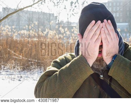 Man Breathing In Winter Forest. Adult Man Wearing Knit Hat, Closes His Face By The Hands Breathing C