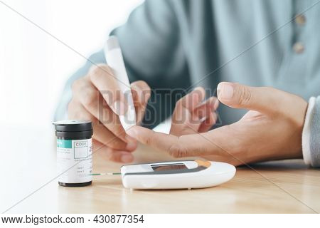 Asian Man Using Lancet On Finger For Checking Blood Sugar Level By Glucose Meter, Healthcare And Med