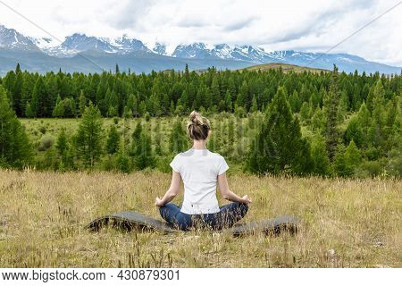 Yogi Woman Practicing Yoga While Sitting In Lotus Position In The Morning In The Mountains