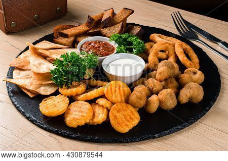 Deef Fried Fresh Beer Plate With Chicken Nuggets, Cheese Fingers, Onion Rings, Sauce On Wood Table.