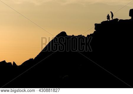 A Pair Of Rock Climbers, Silhouetted At Sunset, Look Back From The Summit Of Stange Edge. Located In