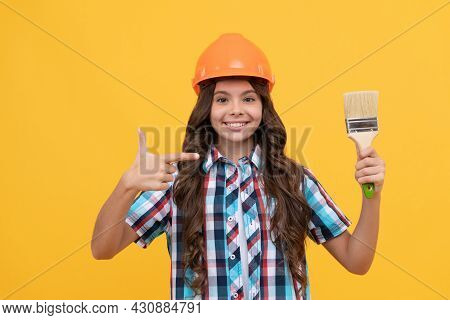 Happy Child With Curly Hair In Construction Helmet Pointing Finger On Painting Brush, Renovation
