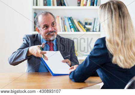 Hispanic Senior Businessman Showing Purchase Contract To Buyer At Desk At Office