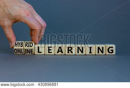Online Or Hybrid Learning Symbol. Businessman Turns Cubes, Changes Words Online Learning To Hybrid L
