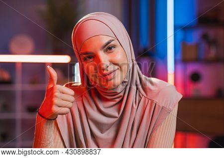 Close Up Of Charming Smiling Likable Young Arabian Woman In Hijab, Sitting At The Desk At Home With