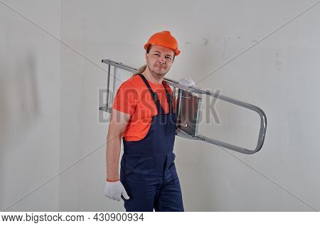 A Worker In Blue Overalls Holds A Stepladder