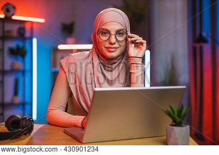 Satisfied Pleasant 30-aged Arabian Woman In Headscarf And Eyeglasses, Sitting At The Desk At Home In