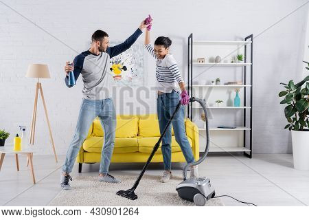Happy Multiethnic Couple With Cleaning Supplies Dancing In Living Room