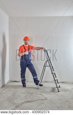 In Overalls, A Superintendent Stands At A Stepladder In A Helmet