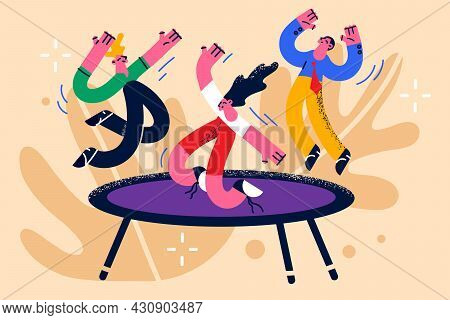 Children Activities And Having Fun Concept. Group Of Happy Kids Jumping On Trampoline Feeling Positi
