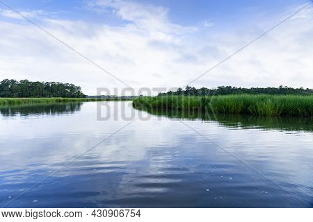 Morning Sun And Blue Sky Reflected In A Centered View Of A Lush Green Salt Marsh Waterway Near Charl