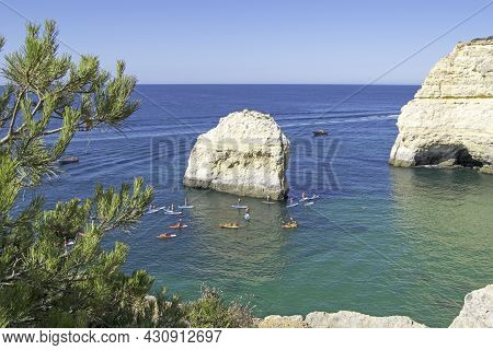 Rock Formations And People Doing Kayaks In The Atlantic Ocean To Visit The Benagil Caves Seen From A