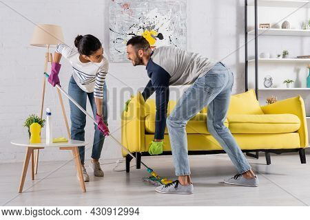 Cheerful Multiethnic Couple Cleaning Floor Under Couch At Home
