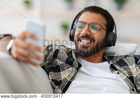 Handsome Arab Guy Watching Movie, Using Wireless Headset And Cellphone