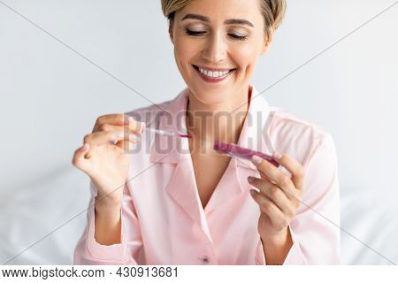 Smiling Woman Holding Lip Gloss And Looking At Tube