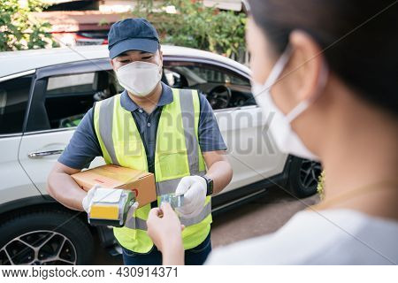 Asian Delivery Man Accept Credit Card Using A Credit Card Reader While Delivering Products To Custom