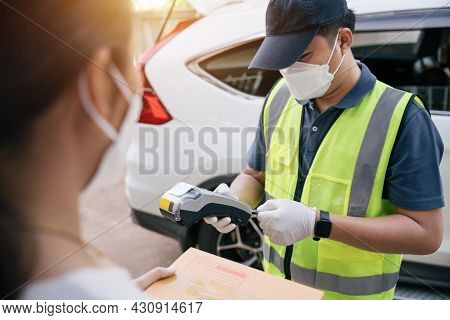 Asian Delivery Man Using A Credit Card Reader While Delivering Products To Customers At Home, Delive