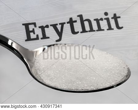 Silver Spoon With Crystalline Erythritol Sugar In Front Of The Word Erythrit