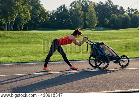 Sporty Woman While Motherhood With Her Son In Baby Carriage Is Doing Fitness And Workout At City Par