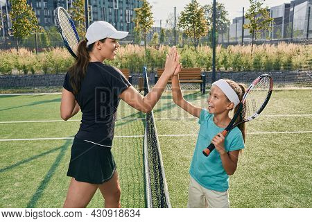Child Gives Five To Her Coach After Playing Tennis. Tennis Training For Children On Outdoor Court