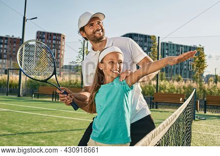Tennis Lesson For A Child. Tennis Coach Teaches Little Girl To Play Tennis On Grass Court