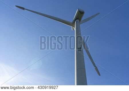 Wind And Renewable Energy Mast With Its Large Propellers And Turbines On A Background Of A Clear Blu