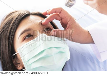 Doctor Checking The Eyes Of A Woman Patient, Which Wearing A Surgical Mask, To People Health Care An