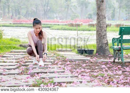 Wide Shot Of Asian Sport Woman Tie Shoelaces On Walkway With Flower On Floor In Part Or Garden Durin