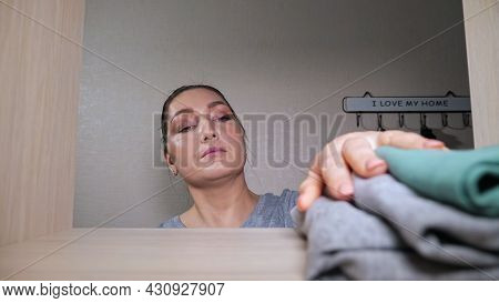 Young Housewife With Hair Bun Puts Washed Folded Clothes On Wooden Shelf In Contemporary Light Walk-