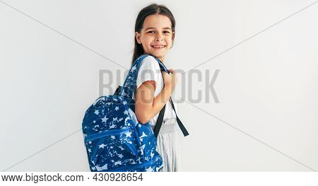 Side View Of Positive Schoolgirl With Blue Backpack Smiling And Looking At Camera. Pretty Schoolkid
