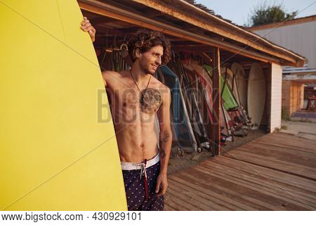 Young european surfer standing on wooden platform and holding surfboard. Smiling curly man with tattoo wear swimming trunks. Concept of extreme water sport. Idea of summer vacation. Sunny daytime