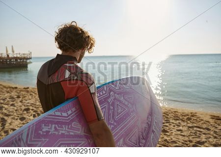 Back view of surfer carrying surfboard to sea water on sandy beach coast. Curly man wear diving suit. Concept of extreme water sport. Idea of summer vacation. Sunny daytime