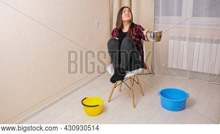 Upset Woman Collects Water Coming Down From Ceiling Of Upstairs Neighbors Into Saucepot Sitting On C