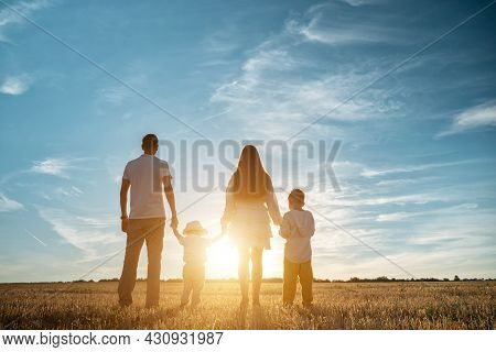 Family With Children Sons Stands Joining Hands Along Shadowed Field At Back Setting Sun In Summer Un