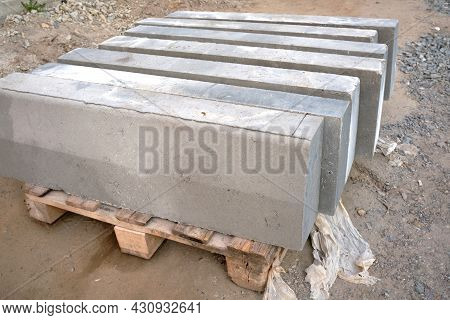 Stack Of Gray Curbstone On Pallet Standing On Pavement. The Pallet With A Stack Of Concrete Curbston