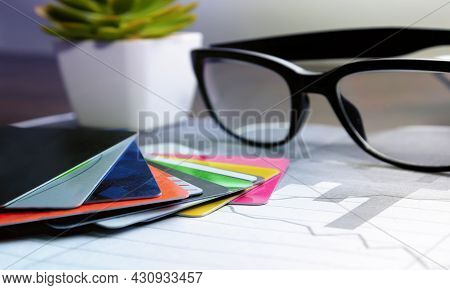 A Stack Of Credit Cards On The Table With Glasses. The Concept Of Banking Operations With Cards.