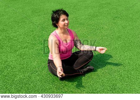 Young Sturdy Chubby Woman Meditates On The Green Lawn After Exercising
