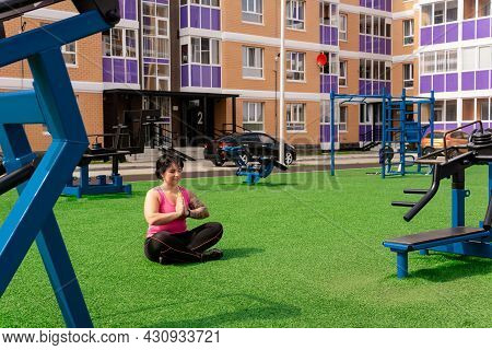 Young Sturdy Chubby Woman Meditates On The Green Lawn After Exercising In The Courtyard Of A City Ho