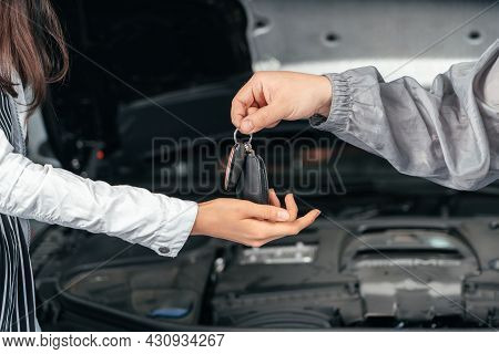 Man Giving Client Keys To Her Repaired Car In Auto Repair Service