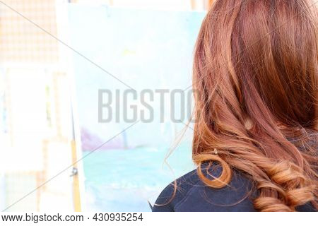 Young Red Hair Girl Painting On Canvas. Back View