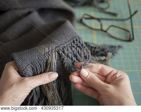Artisan Is In Action. Woman Is Creating A Fringe On A Woolen Scarf Or Muffler. Hands Of Artisan With