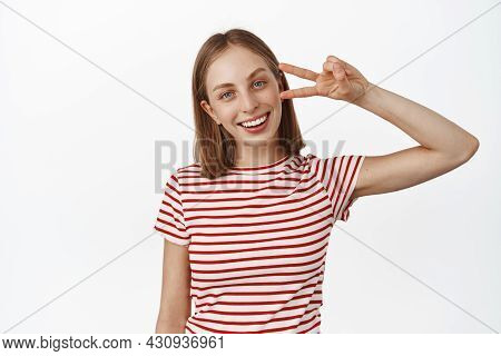 Portrait Of Blond Positive Woman, Girl Showing Peace V-sign And Smiling Broadly With White Perfect T